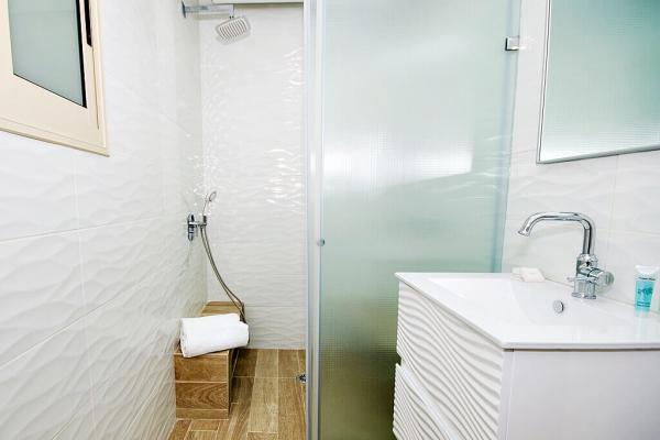 חדר רחצה בעיצוב מודרני בקווים לבנים ונקיים