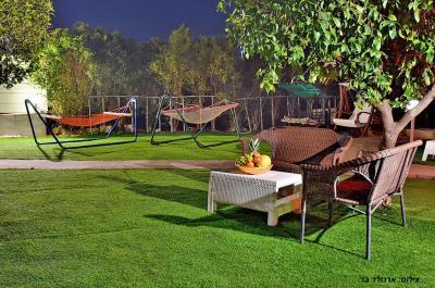 חצר מטופחת מוארת בתאורת גן קסומה