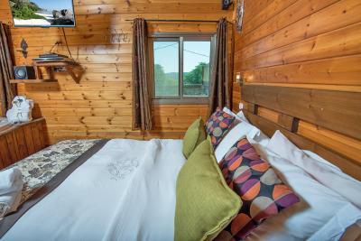 בבקתה בגליל תהנו ממיטת עץ זוגית עם מצעים לבנים ומלטפים