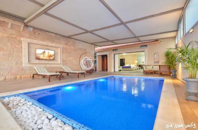 בריכת שחייה בנויה מחוממת ומקורה בחורף בעלת רצפת פסיפס וחלוקי נחל