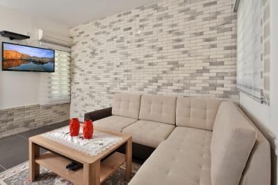 סלון מפואר עם קיר בריק יפהפה מול מסך LCD גדול