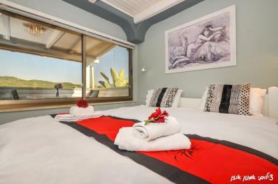מיטת קינג סייז ענקית לצידה חלונות ענקיים המכניסים את הטבע הגלילי פנימה