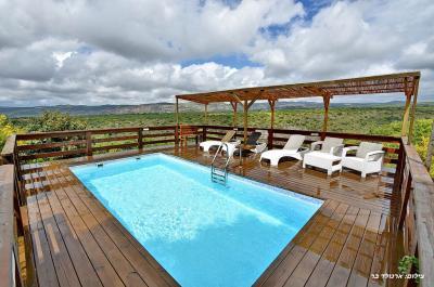 בריכת שחייה גבוהה מול הנוף לצידה מיטות שיזוף וסככת עץ מיוחדת