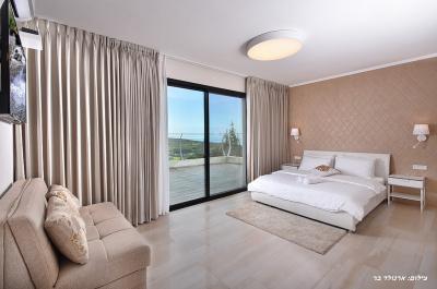 מיטה זוגית בחדר היפהפה של הוילה עם מרפסת הצופה אל נוף הרים
