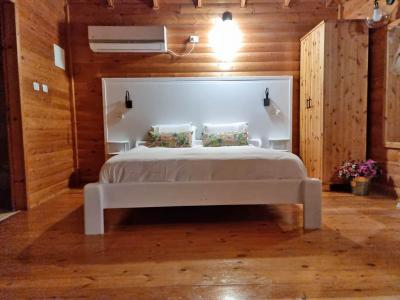 מיטה זוגית מוצעת מצעים איכותיים עם חלוקי רחצה וכריות נעימות