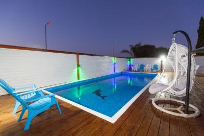 הבריכה גדולה ומפנקת סביבה דק איכותי, פינות ישיבה ומיטות שיזוף