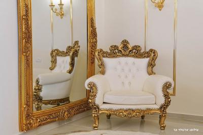 כורסא יוקרתית לצד מראה מוזהבת